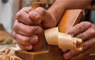 photo d'une main en train de raboter du bois