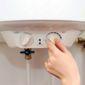 Main qui règle une chaudière basse température