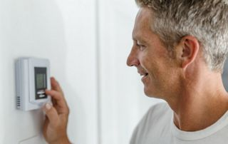 Homme qui règle son thermostat