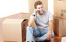homme au téléphone devant ses cartons de déménagement