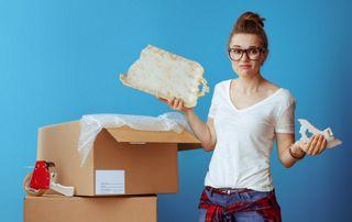 Jeune femme avec un plateau cassé lors d'un déménagement
