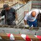 Ouvriers construction mur habitation