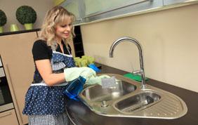 Femme de ménage qui nettoie un évier