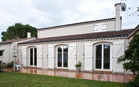 maison avec fenêtres et volets en bois