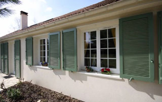 Maison avec fenêtres en PVC et volets verts