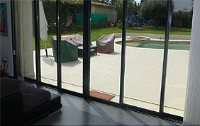 châssis en aluminium sur porte vitrée devant terrasse