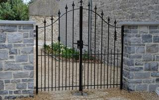 portail fer forgé et colonnes en pierres