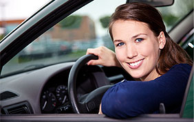 femme souriante au volant de sa voiture