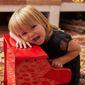 Petite fille blonde avec une robe sur un piano rouge