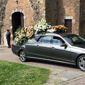 Corbillard devant bâtiment religieux avec des gerbes de fleurs