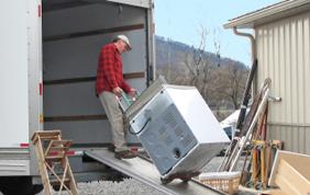 déménageur en train de faire entrer une machine dans le camion de transport