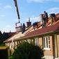 couvreurs sur un toit avec grue