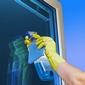 main avec gant jaune nettoyant une vitre