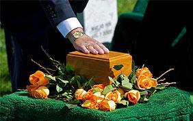 Urne funéraire avec une main posée dessus et des roses orangées