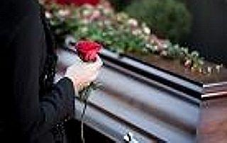 femme tenant une rose rouge devant un cercueil