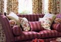 Canapé en tissu bordeau ligné et tentures aux motifs fleuris