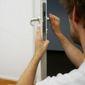 serrurier répare une porte