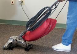 Professionnel qui passe l'aspirateur sur un tapis