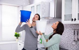 Couple qui récupère l'eau d'une fuite