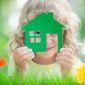 Fillette avec une maquette de maison verte