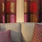 canapé gris avec coussins à motifs devant rideaux colorés