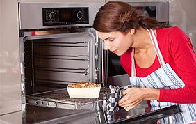 cuisinière qui sort un plat du four